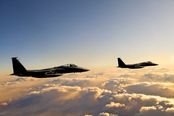 Defense Sector: F-15 Eagle fighter jets flying above clouds at sunset