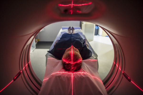 Medical Sector: Patient lying inside a medical scanner in hospital